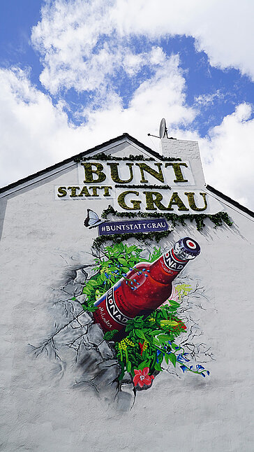 Ambient advertising, large Greenwood moss letters on a house wall, organic soft drink street art campaign